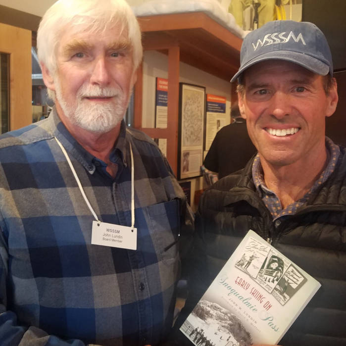 John W. Lundin, founding member of the museum and serves on its Board of Directors, and U.S. Olympic Skier and medal winner, Phil Mahre, holding John's book at the second anniversary celebration of the museum, October 2017. Profits from the Snoqualmie Pass book go to support the museum.